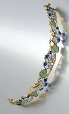 Vever - An Art Nouveau enamel and diamond bracelet, circa 1905. Of openwork foliate design, modelled as a series of blue and frosted colourless plique-à-jour enamel triple flower-heads with metallic foil inclusions, to further shaded green plique-à-jour enamel leaves, with French marks for gold, signed Vever Paris.