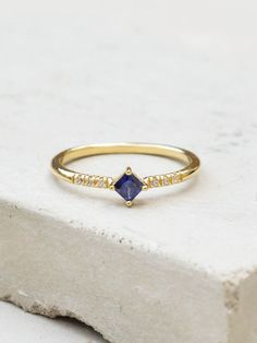 This ring is a gorgeous compliment to our other stacking rings. The ring features one small 3mm princess cut stone on a half band eternity ring. This ring looks great on its own for a clean, feminine