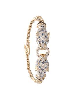 Armband in 585 Gelbgold.  Den Eye Catcher bilden zwei Pantherköpfe. Der Panther charakterisiert ein wildes und elegantes Wesen, das seine Anmut auf den Schmuck und seine Trägerin überträgt. Dargestellt in 8/8 Diamanten ca. 0,30ct und geschmückt mit Saphiren.