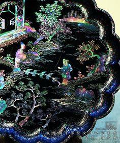 清早期 嵌螺钿牛郎织女图轮花形盘 螺钿,是指用用螺或贝类磨制为薄片,根据在不同的表面进行既定图案的镶嵌技法的总称.往往根据贝、螺的不同,在不同的器物表面会有或素净或绚丽的种种表现,比如这个漆