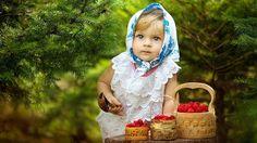 Обои Девочка в платочке на голове сидит на фоне соснового леса возле столика с лукошками, наполненными спелой красной малиной и держит в руке деревянную расписную ложку