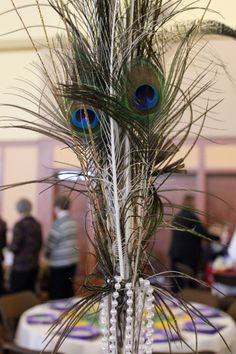 Peacock feather & Mardi Gras beads in flute used as reception centerpiece