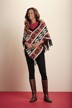 Snowflake patterned poncho accented with warm tones and swinging fringe!