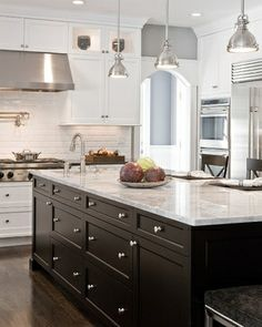 Stove hood, and lights over the bright marble with dark cabinets