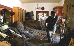 Millions without water in Santiago after floods and landslides cause havoc in Chile - Photo: Men work to salvage belongings from a home full of sludge after the overflow of the Estero San Jose River in San Alfonso, Santiago, Chile, Sunday, February 26