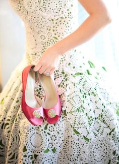 A coloured underskirt has a skirt of stitched together fabric doilies over the top. I love this and the pink contrasting shoes are just fab. Much kudos this clever bride. Image - Sarah London