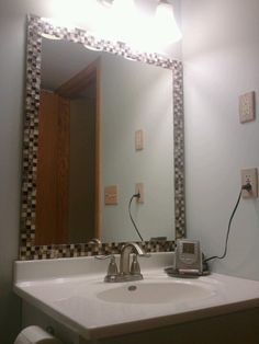 Glass mosaic tiles around bathroom mirror. Can't wait to finish the rest of the bathroom.