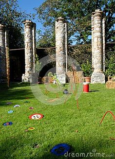 Photo taken inside the park that is in the back of the castle of Strassoldo Friuli (Italy). In the image you see in the foreground on a green lawn where there are various game objects colored. In the background you can see four columns biache, branches of trees and the blue sky.