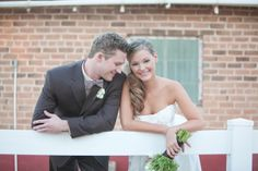 bride-groom-leaning-railing-farm-casual