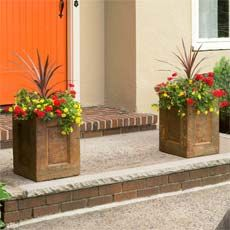two concrete planters with colorful flowers on the entryway of a house to illustrate How to Make a Concrete Planter for this old house