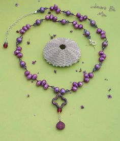 Purple faceted pearls, swarovskis, raspberry chalcedony, purple dyed mother of pearl clover flower...all hand knotted on silk