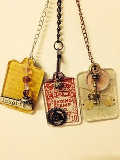Charms made with Tim Holtz fragments charms.  Glue paper to back of charm with glossy accents, trim edges when dry.  Glue embellishments to top of charm with glossy accents.  Chain is from Tim Holtz.