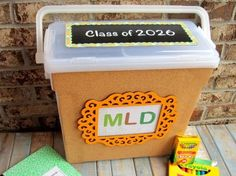 School keepsake organizer, but use a bigger box.   I like that she has notes on the front for special memories (signature for handwriting sample, class schedule, favorite things...)