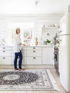 Efter många timmars skissande kom hon och Peter fram till att de kunde använda det dåvarande vardagsrummet som matsal och bygga till en del där ett nytt vardagsrum kunde få plats. Maria gillar enkelhet i inredningen. I köket skippade hon överskåp för att få en luftig känsla. Väggarna klädda med vitmålad råspont ger rummet en lantlig karaktär. Köksskåp, Ikea. Matta, Rugvista. Lerkruka från Hjärtats rum i Dala-Järna. Spis och kyl, Smeg. Scandinavian Cottage, Interior Stylist, Decorating Blogs, Beautiful Kitchens, Cottage Style, Kitchen Dining, House, Inspiration, Home Decor