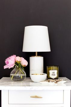 Elegant and simplistic bedside table with lamp and flowers.