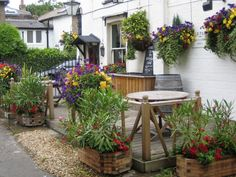 Nice restaurant, café or pub patio with lots of flowers hanging and planters.   Just needs a few umbrellas and some evening landscape lighting!
