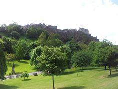 Edinburgh Castle rising above the treetops in Princes Street Gardens.