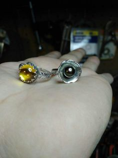 2rings stones set...9 1/2 size yellow synthetic diamond Cab set in sterling silver...7 1/4 size sterling flower multi-colored genuine Tahitian Pearl..these are for sale on my page on facebook...