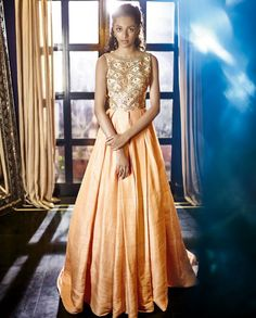 EXCLUSIVE: Subtle peach gown with gota patti embroidery adorning the bodice. Box pleats accentuate the gown with long train at the back. Wash Care: Dry clean only