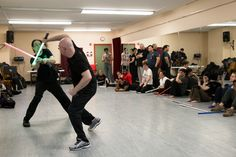 Russ Briggeman Jr., left, and Daniel Reiser perform a choreographed lightsaber fight in front of class members. New York Jedi, photo credit WSJ.com