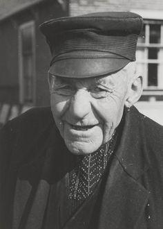 Boer uit Huizen in opknapdracht. Onder de halsopening van zijn vest draagt hij een befje, gebreid met kraaltjes. Het befje onttrekt de 'kiel' (overhemd) aan het oog. Hij draagt een pet en oorringen. 1945 #NoordHolland #Huizen