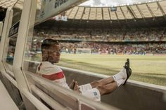 A distracted Alex Oxlade-Chamberlain watches on, hoping that he'll be fit to play for the Three Lions.