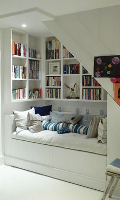 reading nook under the stairs; put mirror on back wall to enhance light. Can bookshelves be inset to make it more comfortable to lean back? Storage under seat? For blankets. Wainscotting?