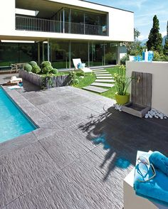 Dalles de terrasse et de cheminement, margelles de piscine et fontaine murale, en pierre reconstituée Ardoisière. ©Pierra