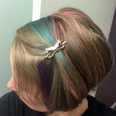 Short, colorful hair streaked with pink and blue, featuring the new flexi of the month from Lilla Rose- Angel Wings.