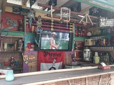 Backyard tiki bar/ Lounge with pirate flags, Margaritaville concoction maker, Tiki statues, metal fish, margarita glasses, frozen drink glasses Norwegian Cruise glasses, Japanese glass floats, beads from New Orleans Bourbon Street, Corona beer lays, a skull, bamboo, LandShark lager, margaritaville Party tub and Tiki signs etc...