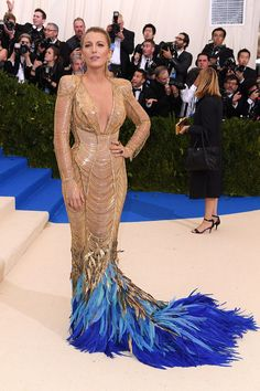 Blake Lively rarely fails to look stunning on the red carpet. And on Monday she glittered at Met Gala, donning a fierce gold and blue gown which featured layers of chains and fluttering feathers. Gala Gowns, Gala Dresses, Carolina Herrera, Saris, Beautiful Dresses, Nice Dresses, Formal Dresses, Blake Lively Style, Blake Lively Dress