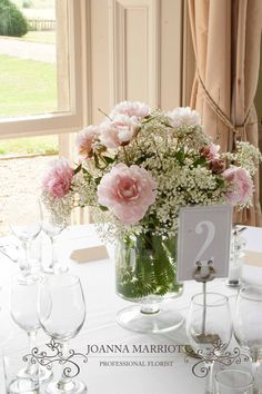 Pink peonies and gypsophila table arrangement. Summer wedding, pastel colours.