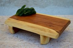 This unique wooden cutting board could be a great addition to your kitchen. Each cutting board is completely handmade and with precision to detail. To make it, we have used a piece of high quality mulberry wood finished with hand rubbed linseed oil. This cutting board is food safe - only natural materials are used - wood and linseed oil. You can use it also as a serving platter. Size approximately: length: 11,7 in.(30cm.) width: 7,8 in.(20cm.) height: 2,34 in.(6cm.)