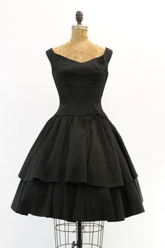 Irresistible 1950s little black dress! Super flattering fitted bodice with a semi-dropped waist. Ultra full double layered tiered skirt. Layers of