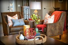 This Contemporary Living Room shows just how much a few accent pieces can do to liven up your decor. Even though there are neutral brown chairs and coffee table, pillows and other pieces of decor bring brightness and fun to the space designed by Fluff Interior Design and Fluff Your Stuff