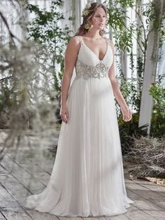 Maggie Sottero - PHYLLIS, Romance is found in this stunning tulle sheath plus size wedding dress, with plunging neckline and sparkling Swarovski crystal embellishment at the waist. Intricate patterns of beaded embroidery adorns a daring illusion back. Finished with crystal button over zipper closure.