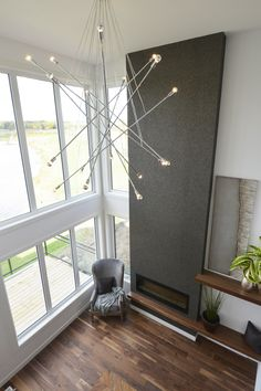 Minimal duplex decor and lighting ideas. Feature wall with electric fireplace and two story windows.
