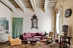 The Rome apartment of pianists Katia and Marielle Labèque was renovated by architect Alessio Lipari and decorated by Axel Vervoordt. In the living room, an antique Italian mirror hangs above the slipcovered Vervoordt sofa, and a bronze Thai Buddha torso is displayed on a sculptor's pedestal | archdigest.com