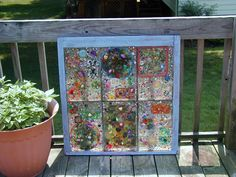 Melted plastic tiles, beads, marbles etc incorporated into a mosaic on an old, chippy window.