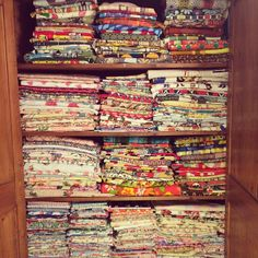 Some colorful vintage fabric. Brown shelving works to calm the stash