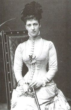 The bustle of Alexandra's dress emerges from the right side while the buttons define the extent of her cuirasse bodice.