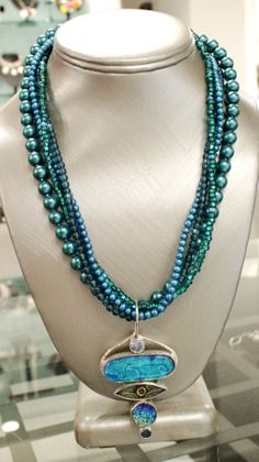 """Emerald Peackcock"" pendant, No. 142, signed, handmade, has 7 layers of fused glass including vintage 1940's button, druzy quartz crystal, semi-precious blue topaz.  Necklace is 4 strand, 18"", sterling clasp; teal blue glass pearls, green seed beads, 1940's two-toned glass beads, and aqua fresh-water pearls.  Please inquire for price and availability."