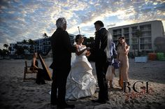 South Florida Officiant Rev. Paul K. Underhay performs destination wedding ceremony at The Four Seasons Palm Beach under blue skies with harpist Esther Underhay