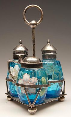 """BARREL - HONEYCOMB-OPTIC THREE-PIECE CONDIMENT SET, blue with polychrome floral and traces of gilt decoration, comprising a salt and pepper shaker with matching period two-part lids, and a mustard pot with period lid. Fitted in a quadruple-plate stand marked """"E.G. WEBSTER & SON / N.Y."""" Fourth quarter 19th century."""