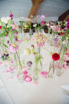 Ein paar schlichte Glasflaschen, ein paar Sommerblumen und eine wundervolle Tischdekoration für Sommerhochzeiten