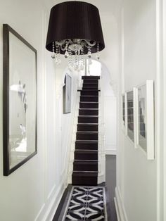 Glamorous black and white hallway with crystal and black drum shade chandelier. Soft white walls, dark hardwood floors and black and white geometric rug runner. White stairways and bannister with black runner.