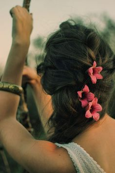 Bright coral pink Hawaiian flowers in braid