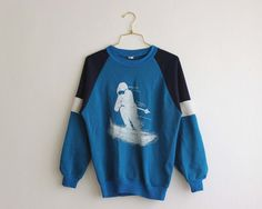 cool sweatshirt with a snow surfer print in white on a light blue and navy soft and warm fabric. elastic waist at the neck and wrist.