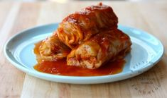 3 stuffed cabbage rolls piled on white plate topped with tomato based sauce