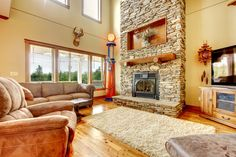 Large family room with stone fireplace, vaulted ceiling, extensive use of wood and brown leather furniture